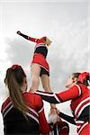 Cheerleaders holding girl up