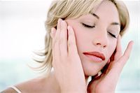 Woman touching her face Stock Photo - Premium Royalty-Freenull, Code: 679-02995583