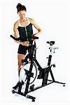 Woman Adjusting Stationary Bicycle                                                                                                                                                                       Stock Photo - Premium Rights-Managed, Artist: Angus Fergusson          , Code: 700-03004414
