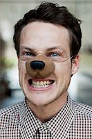 man with toy dog nose snarling Stock Photo - Premium Royalty-Freenull, Code: 649-03008913