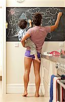 father and son drawing on chalkboard Stock Photo - Premium Royalty-Freenull, Code: 649-03010123