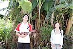 Couple looking up a tropical tree                                                                                                                                                                        Stock Photo - Premium Rights-Managed, Artist: Aflo Relax               , Code: 859-03036081
