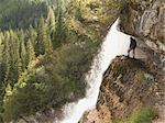 Person standing near waterfall on cliff