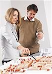 Man and woman at architectural model Stock Photo - Premium Royalty-Free, Artist: Blend Images, Code: 628-03058858