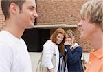 Two teenage girls gossiping about two teenage boys Stock Photo - Premium Royalty-Free, Artist: Blend Images, Code: 628-03058864