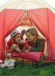 Mother and Daughter Eating inside Tent