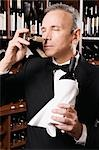 Businessman smelling cork of a wine bottle                                                                                                                                                               Stock Photo - Premium Rights-Managed, Artist: Glowimages               , Code: 837-03069886