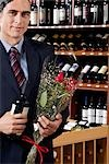 Businessman holding a wine bottle with a bouquet of flowers                                                                                                                                              Stock Photo - Premium Rights-Managed, Artist: Glowimages               , Code: 837-03070353