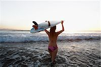 Woman carrying a surfboard on the beach                                                                                                                                                                  Stock Photo - Premium Rights-Managednull, Code: 837-03070415