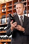 Businessman reading the label of a wine bottle                                                                                                                                                           Stock Photo - Premium Rights-Managed, Artist: Glowimages               , Code: 837-03070531