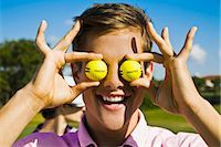 Close-up of a man holding golf balls in front of his eyes,Biltmore Golf Course,Coral Gables,Florida,USA                                                                                                  Stock Photo - Premium Rights-Managednull, Code: 837-03070966