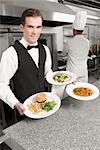 Waiter holding plates of foods                                                                                                                                                                           Stock Photo - Premium Rights-Managed, Artist: Glowimages               , Code: 837-03070979