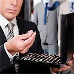 Businessman selecting cuff links in a clothing store                                                                                                                                                     Stock Photo - Premium Rights-Managed, Artist: Glowimages               , Code: 837-03070983