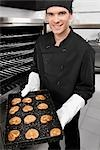 Chef holding a tray of cookies                                                                                                                                                                           Stock Photo - Premium Rights-Managed, Artist: Glowimages               , Code: 837-03071699