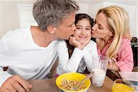 Couple kissing their daughter at a breakfast table                                                                                                                                                       Stock Photo - Premium Rights-Managednull, Code: 837-03072188