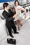 Businessman and a woman reading a newspaper in a laundromat                                                                                                                                              Stock Photo - Premium Rights-Managed, Artist: Glowimages               , Code: 837-03072883