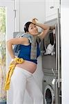Pregnant woman washing clothes and looking tired                                                                                                                                                         Stock Photo - Premium Rights-Managed, Artist: Glowimages               , Code: 837-03073091