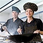 Female and a male chef cooking food in the kitchen                                                                                                                                                       Stock Photo - Premium Rights-Managed, Artist: Glowimages               , Code: 837-03073181