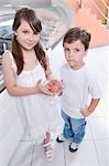Girl holding a glass of ice cream and standing with her brother                                                                                                                                          Stock Photo - Premium Rights-Managed, Artist: Glowimages               , Code: 837-03073214