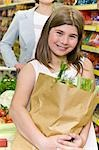 Girl carrying a paper bag of vegetables in a supermarket                                                                                                                                                 Stock Photo - Premium Rights-Managed, Artist: Glowimages               , Code: 837-03073927