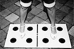 Low section view of a woman standing with her legs apart on dice drawn on the floor                                                                                                                      Stock Photo - Premium Rights-Managed, Artist: Glowimages               , Code: 837-03075075