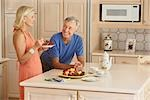 Couple Standing in Kitchen, Eating Stock Photo - Premium Rights-Managed, Artist: Marc Vaughn              , Code: 700-03075347