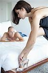 Couple in Bedroom, Woman Putting on Shoes