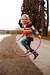 Girl Jumping through Hula-hoop                                                                                                                                                                           Stock Photo - Premium Rights-Managed, Artist: Nick Onken               , Code: 700-03075867