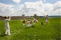 Happy family jump roping in countryside Stock Photo - Premium Royalty-Freenull, Code: 649-03078483
