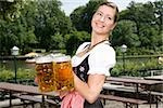 A traditionally clothed German woman serving beer in a beer garden Stock Photo - Premium Royalty-Free, Artist: Cultura RM, Code: 653-03079653