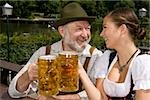 A traditionally clothed German man and woman in a beer garden toasting glasses Stock Photo - Premium Royalty-Free, Artist: Bettina Salomon, Code: 653-03079656