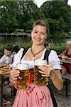 A traditionally clothed German woman serving beer in a beer garden Stock Photo - Premium Royalty-Free, Artist: Beyond Fotomedia, Code: 653-03079665