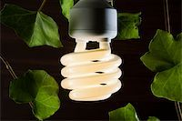 An illuminated energy saving light bulb surrounded by ivy leaves Stock Photo - Premium Royalty-Freenull, Code: 653-03079747