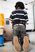 Little boy kneeling on floor in front of plastic bin, rear view Stock Photo - Premium Royalty-Freenull, Code: 632-03083564