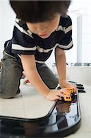 Little boy playing with cars on plastic track Stock Photo - Premium Royalty-Freenull, Code: 632-03083589