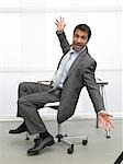Business man sitting on a chair makes a gesture Stock Photo - Premium Royalty-Freenull, Code: 689-03125917