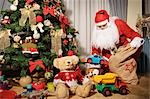 Santa Claus Putting Presents Under Christmas Tree
