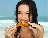 Young women eating a chicken leg                                                                                                                                                                         Stock Photo - Premium Royalty-Freenull, Code: 649-03154163