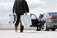 person walking on parking lot - man carrying cases woman waiting in car                                                                                                                                                                  Stock Photo - Premium Royalty-Freenull, Code: 649-03154657