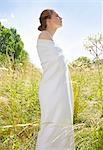 Profile of a young woman standing in a field wrapped in a white pashmina Stock Photo - Premium Rights-Managed, Artist: ableimages, Code: 822-03161723