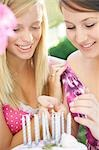 Close up of two teenaged girls lighting candles on a birthday cake Stock Photo - Premium Rights-Managed, Artist: ableimages, Code: 822-03161734