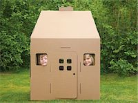 Boy and girl looking out from the windows of a cardboard playhouse Stock Photo - Premium Rights-Managednull, Code: 822-03162092
