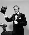 1970s MAN MAGICIAN WEARING VELVET TUXEDO WHITE GLOVES POINTING WAND TO TOP HAT IN HAND