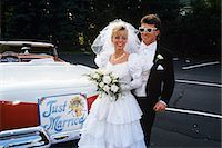 1991 BRIDE AND GROOM STANDING NEXT TO VINTAGE CONVERTIBLE FORD CAR Stock Photo - Premium Rights-Managednull, Code: 846-03163773