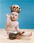 1960s BABY WEARING CLOTH DIAPER AND CROWN OF KING HOLDING A ROYAL MONARCH SCEPTER WAVING WITH ONE ARM RAISED