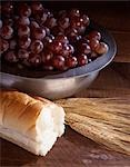 STILL LIFE OF WHEAT BREAD AND GRAPES IN A SILVER BOWL SYMBOLIC OF COMMUNION