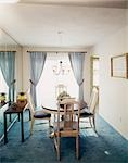 1970s DINING ROOM WITH DINING TABLE FOUR CHAIRS A CHANDELIER AND PALE BLUE CURTAINS