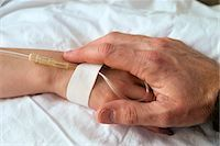 ADULT HAND HOLDING CHILD'S HAND ON HOSPITAL BED Stock Photo - Premium Rights-Managednull, Code: 846-03164942