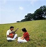1970s YOUNG AFRICAN AMERICAN COUPLE SITTING ON GRASSY HILL MAN PLAYING ACOUSTIC GUITAR