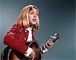 1960s BLOND TEENAGED GIRL SINGING AND PLAYING ACOUSTIC GUITAR